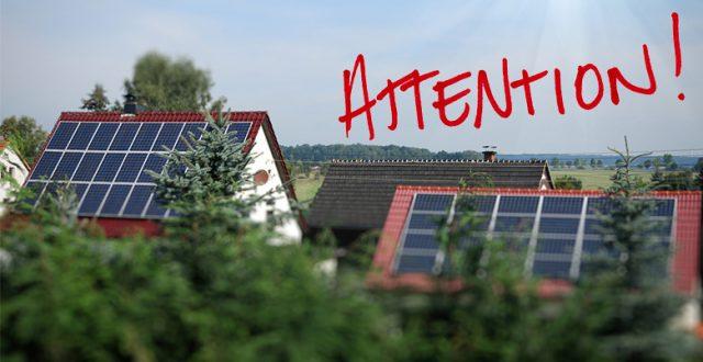 Maison avec panneaux solaires et le mot 'Attention' au dessus.